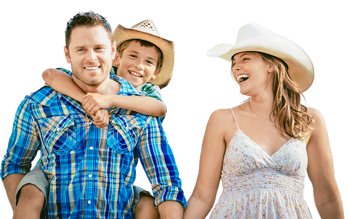 man, woman, and child with cowboy hats