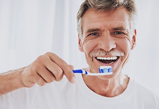 Senior man smiling while brushing his teeth
