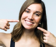 Woman with a dental implant pointing to her smile.