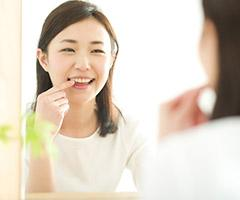 woman pointing to tooth in mirror