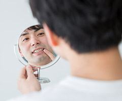 man looking at smile in circle mirror
