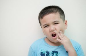 child frowning holding jaw in pain