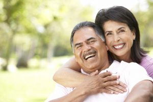 Smiling couple in summer with dental implants in Owasso